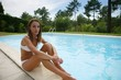 Young woman lounging by the pool