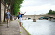 Couple is walking by the Seine embankment in Paris, girl is bala