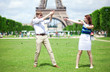 Closeup of happy positive couple playing near the Eiffel tower