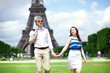 Happy positive couple walking by the Eiffel tower