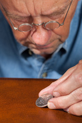 Senior man examining half dollar