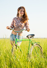 girl with  bicycle in grass