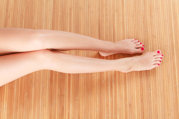 Female legs on wooden floor