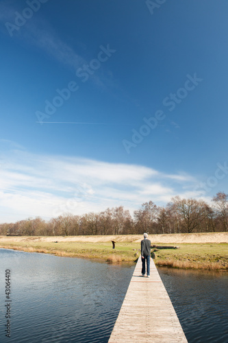 Man walking away over water