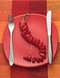 Chili pepper cut in pieces on red plate