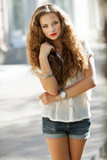 Beautiful young woman with gorgeous curly hair outdoors