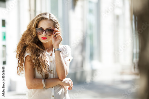Beautiful young woman in sunglasses outdoors