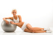 Woman in white fitness outfit exercise ball