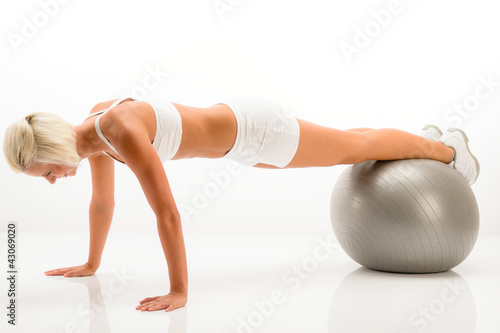 Woman gym ball pushups at white fitness