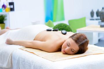 junge frau genießt eine hotstone massage