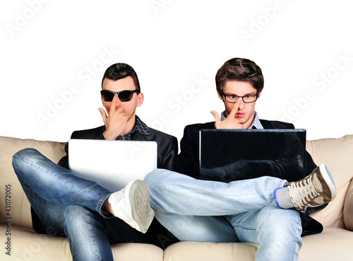 Two young gamers sitting together on sofa and using their laptop