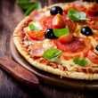 Pizza with salami, tomatoes and ham on wooden board