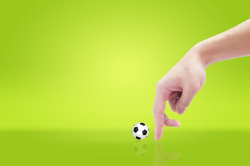 finger and soccer ball on green grass background