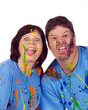 Couple making faces at the camera after a family paint war party
