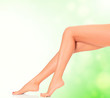 Perfect long female legs on green blurred background.