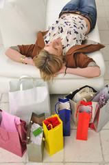 Glückliche Frau liegt auf Sofa mit Einkaufstüten