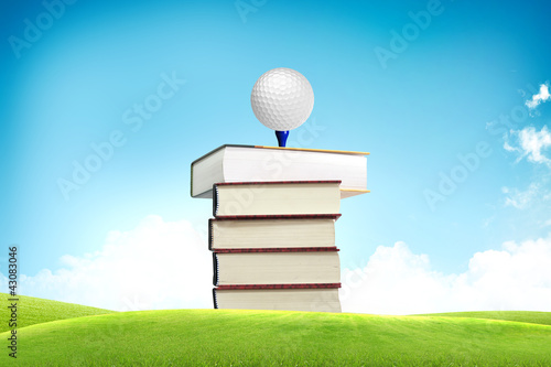 Golf ball on book tee off with green grass field over the blue s
