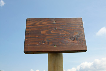 warning sign in wood and the blue sky