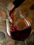 Red wine pouring on stone wall