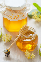 Two jars of linden honey and spoon of honey
