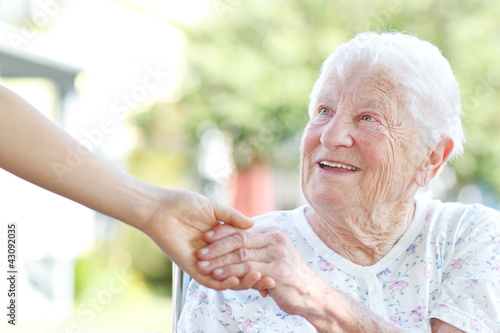 Leinwanddruck Bild Senior woman holding hands with caretaker
