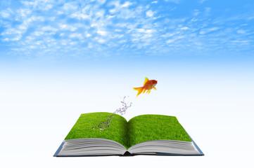 Golden fish jumping across grass water book, conceptual idea