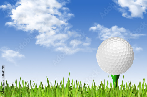 Golf ball on tee off over the green grass and clouded sky