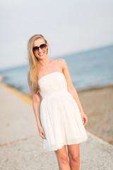 Frau spaziert am Wellenbrecher
