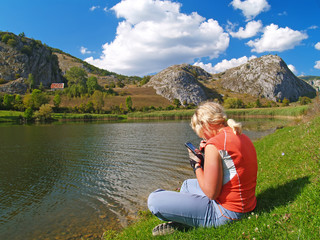 Young blonde woman sitting by the lake
