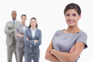 Close-up of a businesswoman smiling and a team crossing their ar