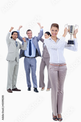 Woman holding a cup with people dressed in suits acclaiming