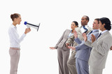 Woman yelling at business people through a megaphone