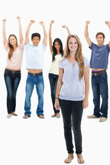 Woman smiling with people with their arms raised behind her