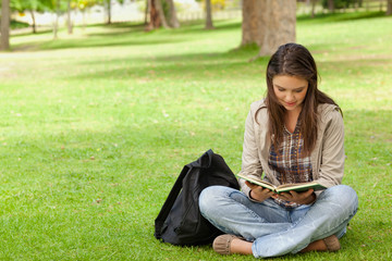 Teenager sitting while reading her textbook