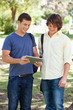 Two smiling male students with an ebook