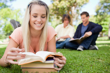 Girl lying while reading books in a park