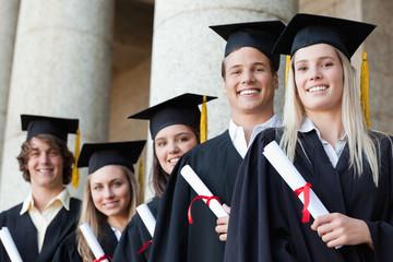Close-up of five smiling graduates posing