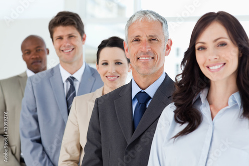 Four smiling employees standing upright around their director