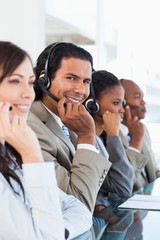 Young smiling call centre worker working among his business team