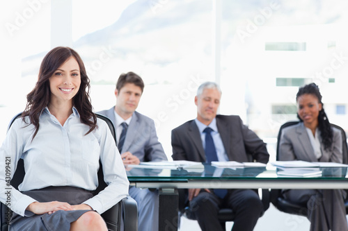 Young businesswoman sitting with her hand on her leg and accompa