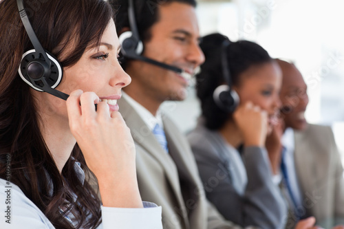Young businesswoman working with a headset and accompanied by he