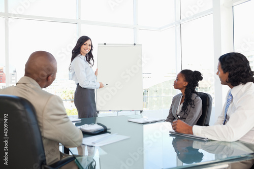 Businesswoman giving a presentation while her co-workers are lis