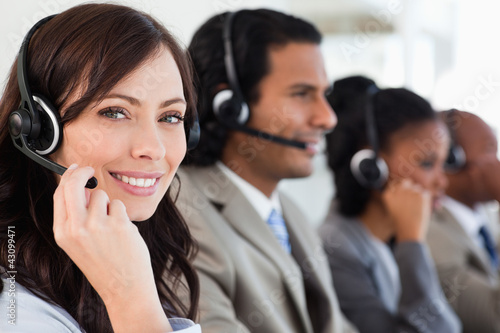 Smiling employee working with a headset while looking at the cam