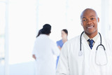 Young doctor standing in a bright room with his team in the back