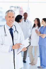 Smiling doctor pointing at a word on his clipboard