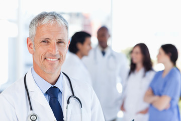 Mature doctor standing upright while waiting for his team