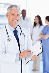Mature doctor showing a beaming smile while pointing to somethin