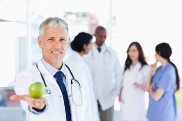 Mature doctor holding an apple in his right hand