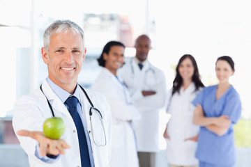 Mature doctor holding an apple while his medical team is looking