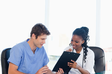Two nurses working on a professional clipboard in a bright room